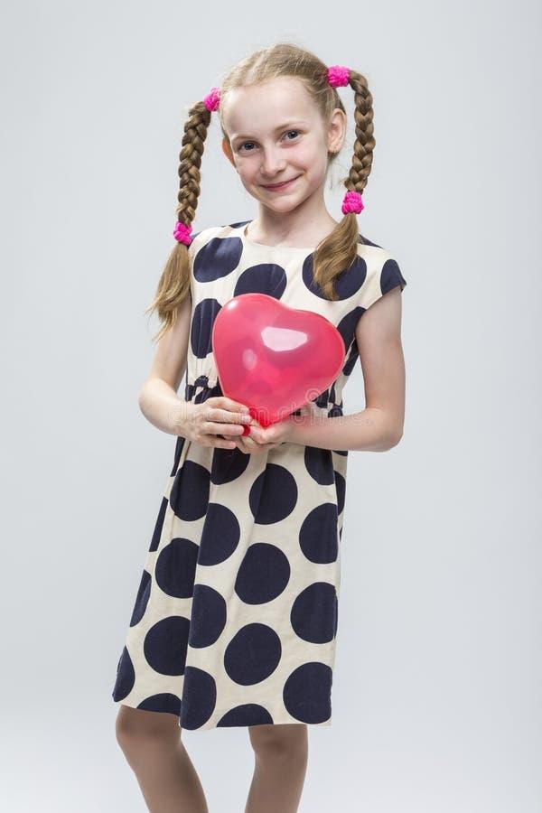 Kaukasisch Blond Meisje met Vlechten die in Polka Dot Dress Against White stellen royalty-vrije stock foto