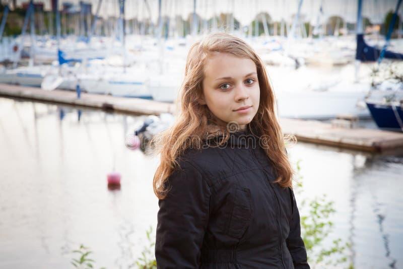 Kaukasisch blond meisje op de meerkust met pijler stock foto