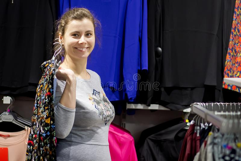 Kaukasisch donkerbruin meisje bij het winkelen het gelukkige meisje nam nieuwe kleding op hanger in modieuze boutique stock afbeeldingen