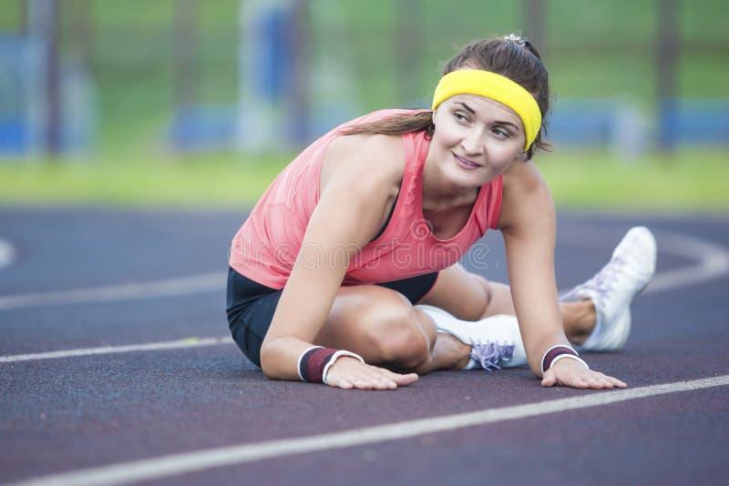 Kaukasisch Donkerbruin Wijfje die in Atletische Sportgear Benen hebben die Excercises in openlucht uitrekken stock foto