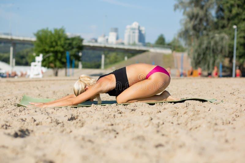 Kaukasisch geschiktheidsmeisje die yoga doen excercises bij het strand royalty-vrije stock afbeelding