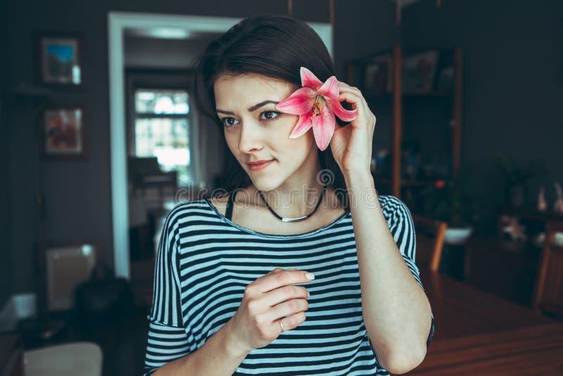 Kaukasisch jong mooi vrouwenmodel met slordig lang haar in gescheurde jeans en gestreepte t-shirtzitting op lijst stock foto