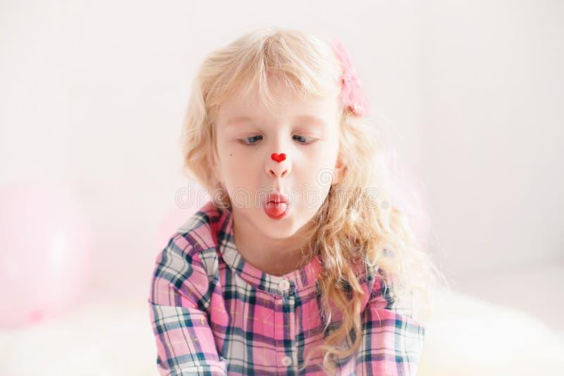 Kaukasisch leuk aanbiddelijk kindmeisje die haar neus met hartsticker bekijken royalty-vrije stock foto
