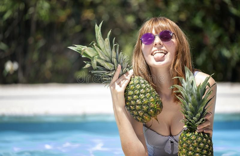 Kaukasisch meisje die met zonnebril twee ananassen in een pool houden stock foto