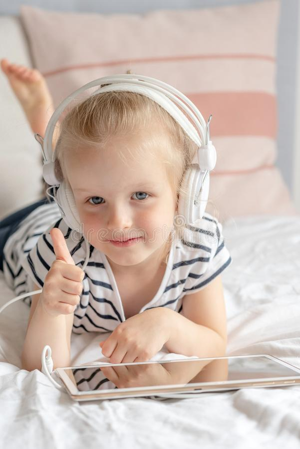 Kaukasisch Meisje in Hoofdtelefoon het Letten op Tablet in Bed stock foto