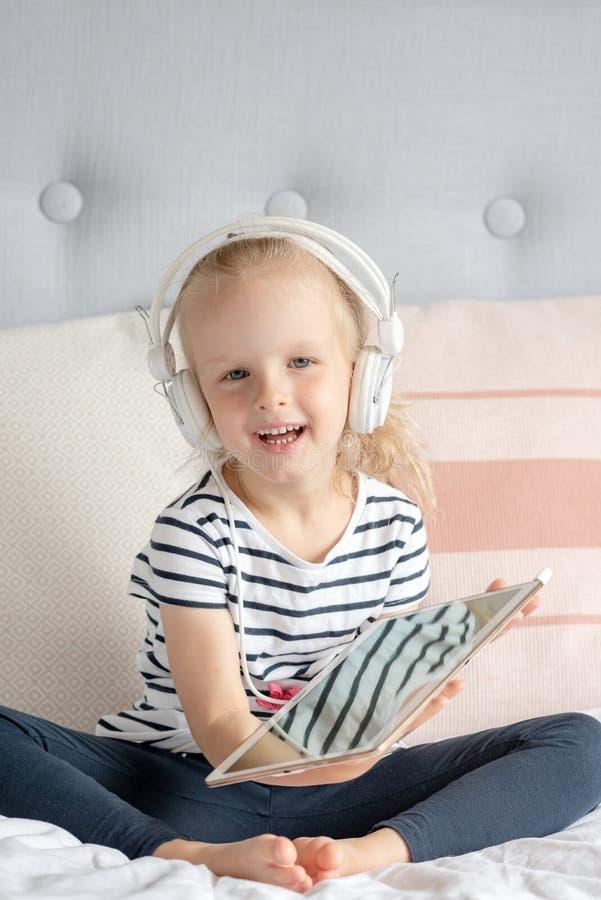 Kaukasisch Meisje in Hoofdtelefoon het Letten op Tablet in Bed royalty-vrije stock afbeelding