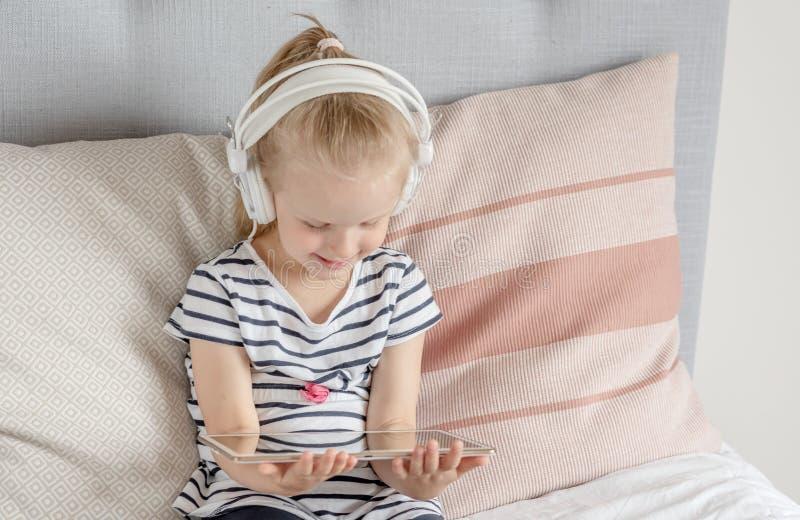 Kaukasisch Meisje in Hoofdtelefoon het Letten op Tablet in Bed royalty-vrije stock foto's