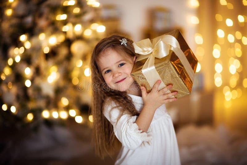 Kaukasisch meisje met de blonde lange gift van haarkerstmis, gouden ligh stock afbeeldingen