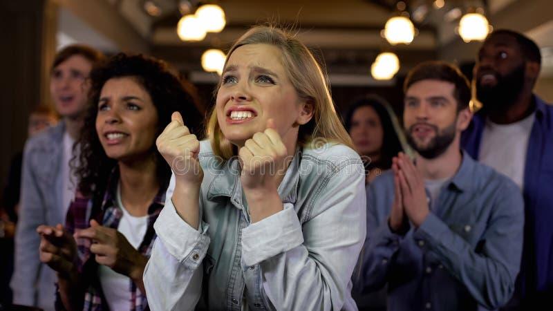 Kaukasisch meisje met haar vrienden die vinger kruisen die op resultaten van loterij wachten royalty-vrije stock fotografie