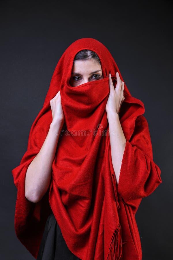 Kaukasisch Meisje omvat in een rode poncho die achter de stof verbergen royalty-vrije stock fotografie