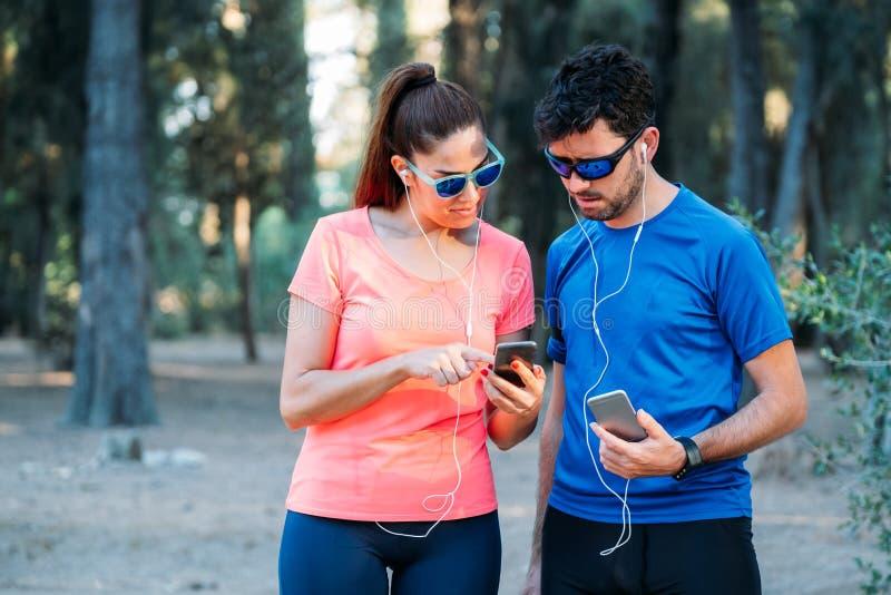 Kaukasisch paar die op mobiele toepassing letten en in een park uitoefenen Gezond het leven concept royalty-vrije stock foto's