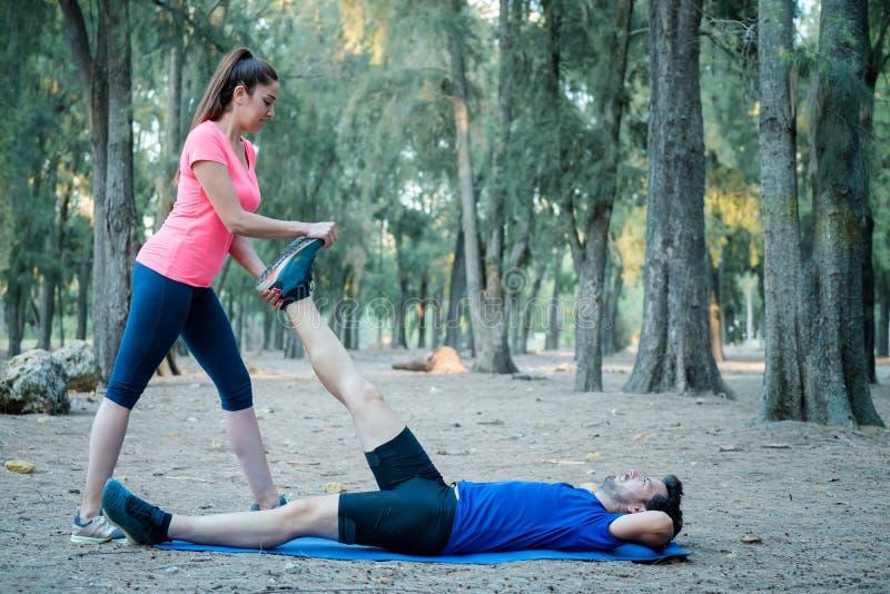 Kaukasisch paar die uitrekkende oefeningen in een park doen royalty-vrije stock afbeelding