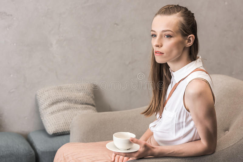 Kaukasisch peinzend meisje met koffiekop zitting en weg het kijken stock afbeeldingen