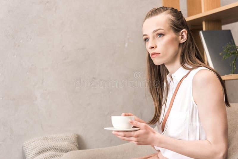 Kaukasisch peinzend meisje met koffiekop zitting en weg het kijken royalty-vrije stock afbeelding