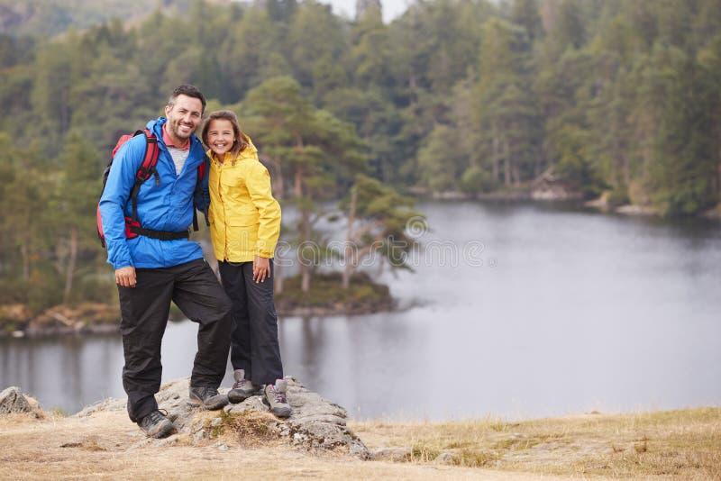 Kaukasisch pre-tienermeisje die zich met haar vader op een rots door een meer bevinden, die aan camera, oever van het meerachterg royalty-vrije stock fotografie