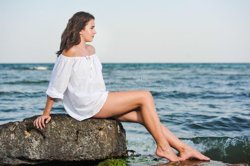 Kaukasisch tienermeisje in bikini en het witte overhemd lounging op lavarotsen door de oceaan stock foto