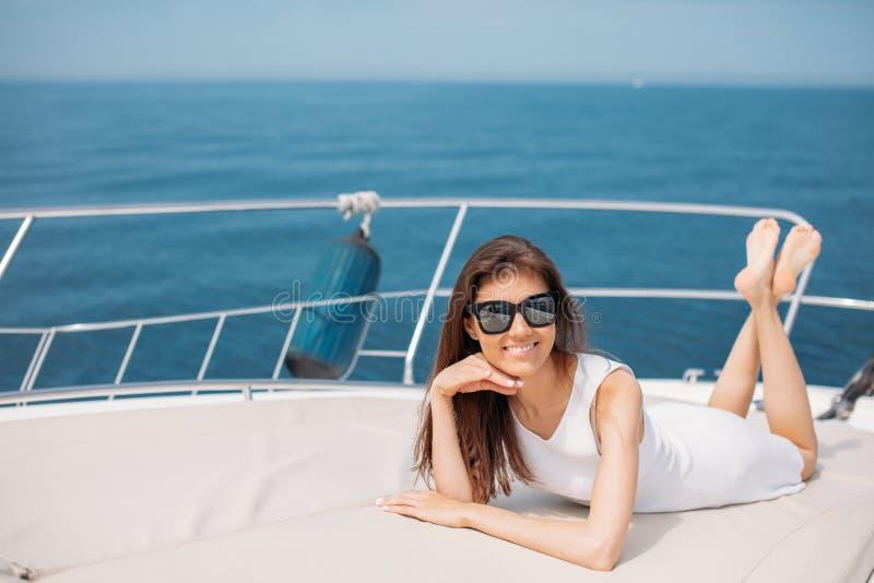 Kaukasisch vrouwelijk model in glazen die op luxe varende boot stellen royalty-vrije stock foto