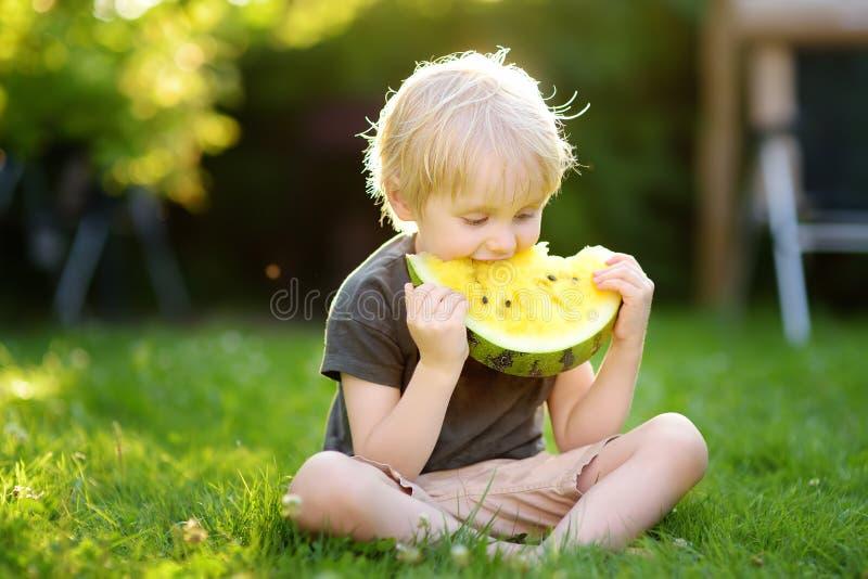 Kaukasisch weinig jongen die met blonde haren gele watermeloen op binnenplaats eten royalty-vrije stock fotografie