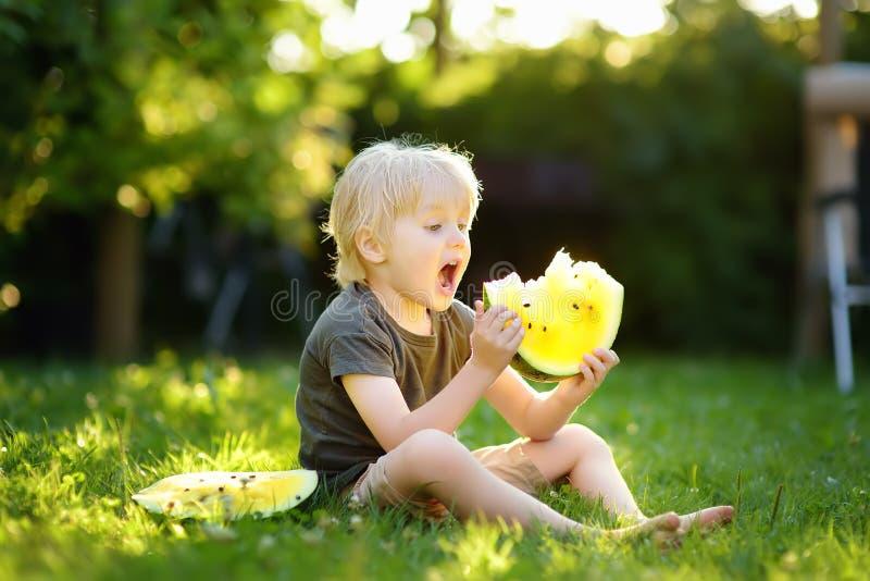 Kaukasisch weinig jongen die met blonde haren gele watermeloen op binnenplaats eten stock fotografie