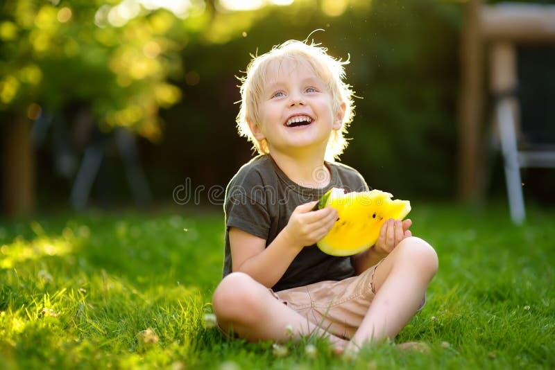Kaukasisch weinig jongen die met blonde haren gele watermeloen op binnenplaats eten stock foto's