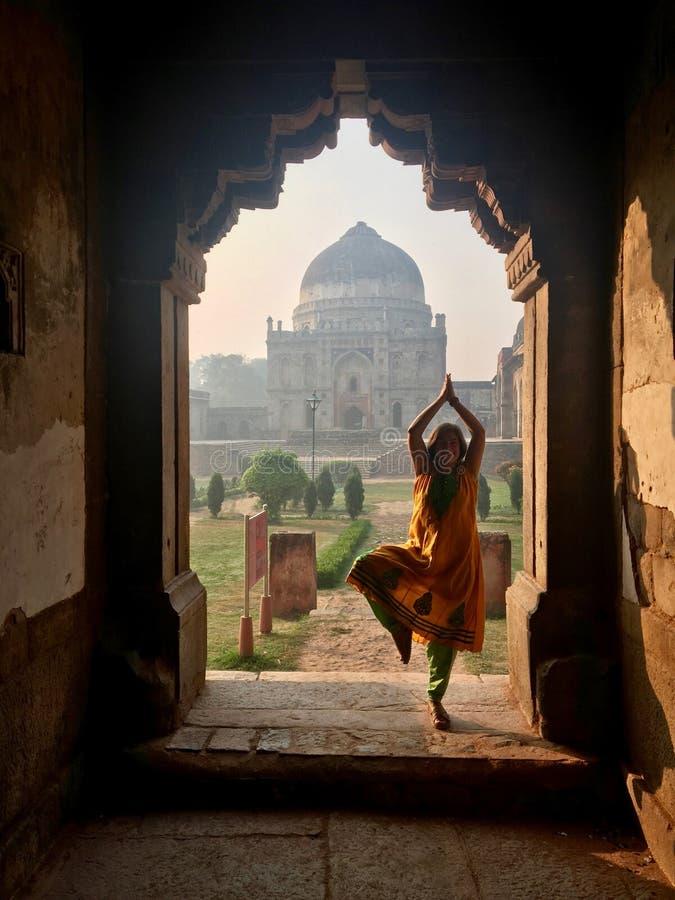 Kaukasisch wijfje die yoga in Bada Gumbad doen Complex bij vroege ochtend in Lodi-Tuin stock afbeeldingen