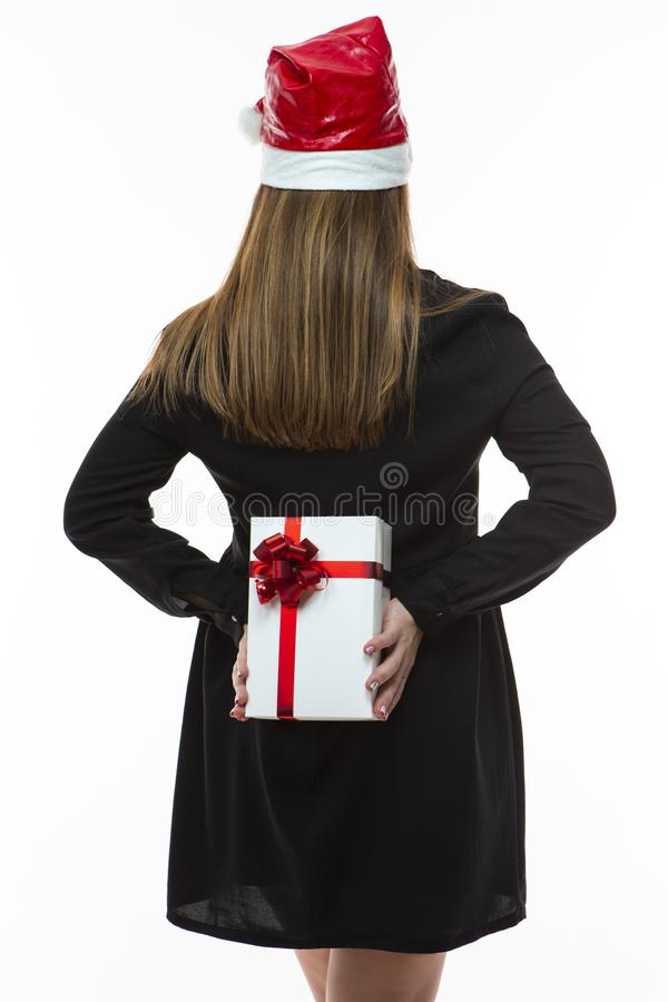 Kaukasisch Wijfje in Santa Hat Holding White Giftbox met Rood Ribon Behind Her Back Geïsoleerd over wit royalty-vrije stock afbeeldingen