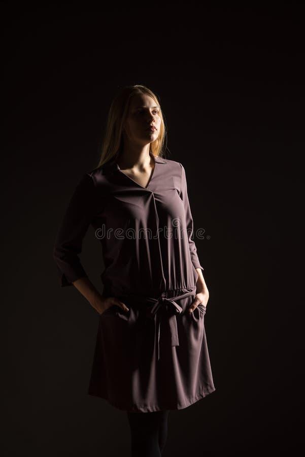 Kaukasisch wit vrouwelijk modelportret Mooi meisje, lang blondehaar Vrouwen stellende die studio op een zwarte achtergrond wordt  royalty-vrije stock afbeelding