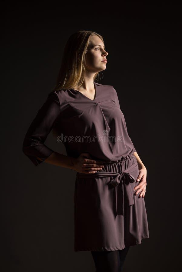 Kaukasisch wit vrouwelijk modelportret Mooi meisje, lang blondehaar Vrouwen stellende die studio op een zwarte achtergrond wordt  royalty-vrije stock fotografie