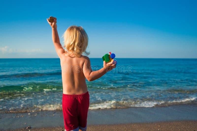 Kaukasische Baby Throwsteine zum Meer stockfotografie