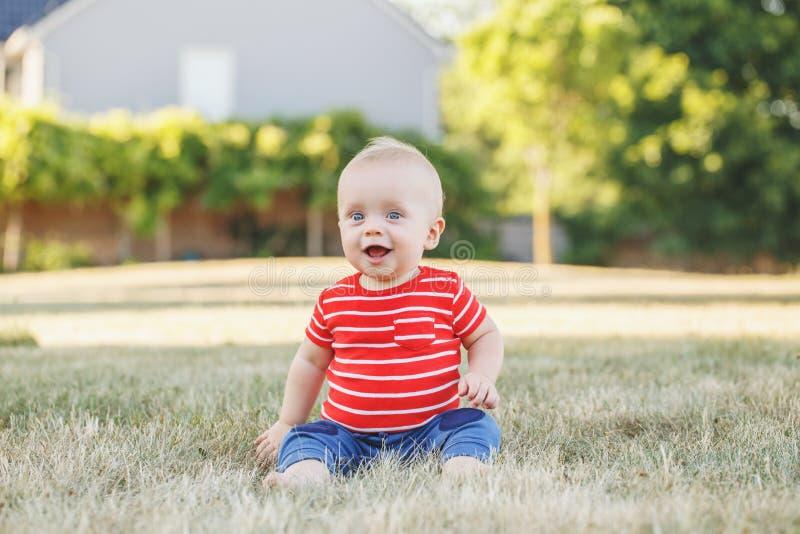 Kaukasische babyjongen in rode t-shirt en broek in gras in gebiedsweide buiten royalty-vrije stock foto