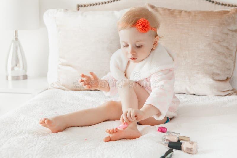 Kaukasische Babymalerei nagelt auf Bett zu Hause sitzen stockfoto