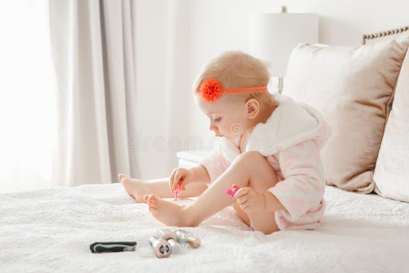 Kaukasische Babymalerei nagelt auf Bett zu Hause sitzen lizenzfreie stockfotos