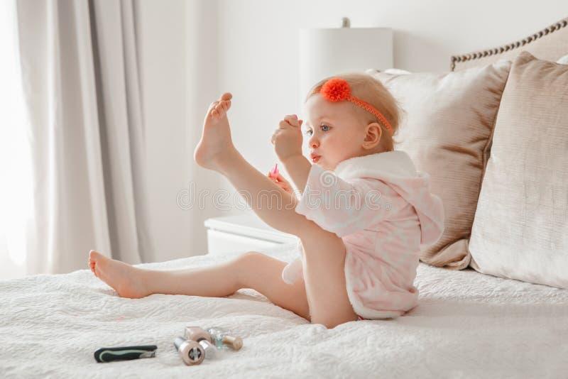 Kaukasische Babymalerei nagelt auf Bett zu Hause sitzen lizenzfreies stockbild