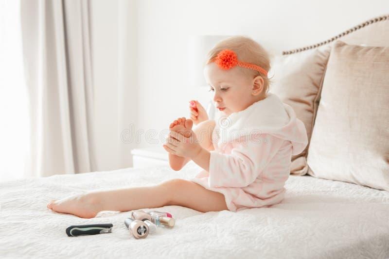 Kaukasische Babymalerei nagelt auf Bett zu Hause sitzen lizenzfreie stockfotografie
