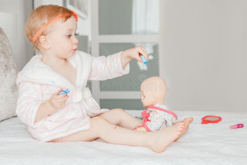 Kaukasische Babymalerei nagelt auf Bett zu Hause sitzen lizenzfreies stockfoto