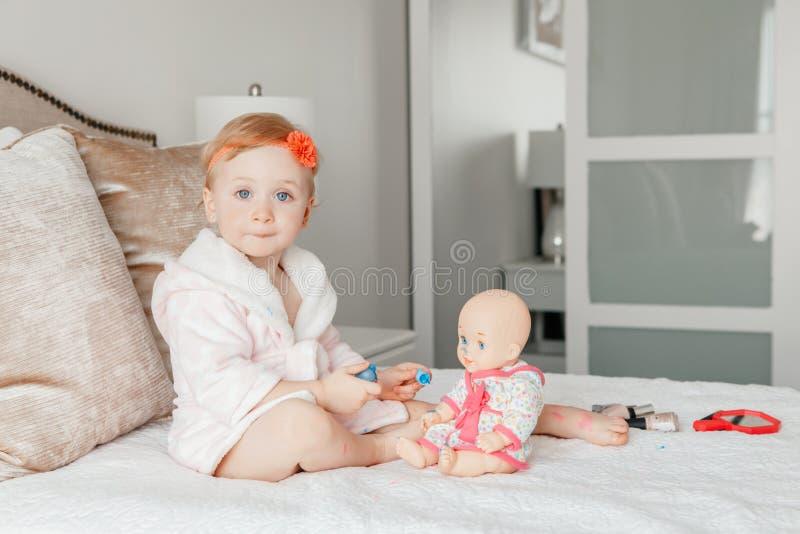 Kaukasische Babymalerei nagelt auf Bett zu Hause sitzen lizenzfreie stockbilder