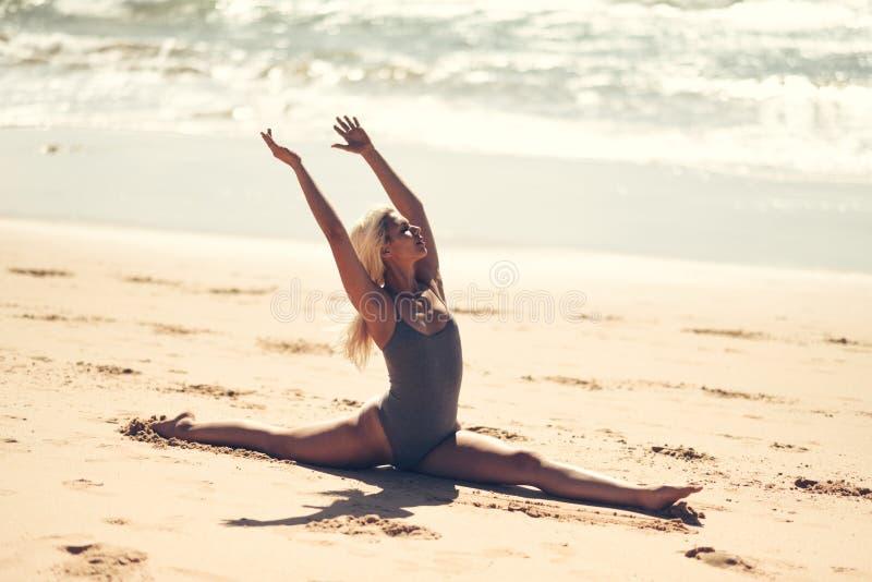 Kaukasische blondevrouw het praktizeren yoga in het strand stock fotografie