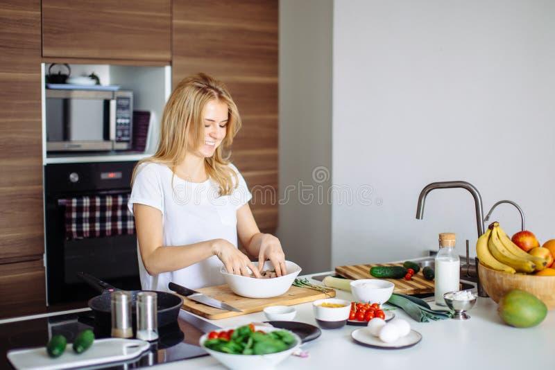 glückliche blondine die mit gemüse in der küche kochen