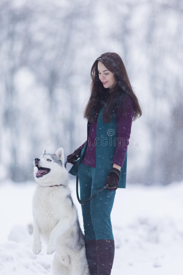 Kaukasische Brunette-Frau, die ihren Husky Dog auf einer kurzen Leine während eines Spaziergangs in der Winterzeit hält stockbilder
