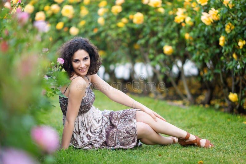Kaukasische brunette junge Frau, die auf grünem Gras in einem Rosengarten nahe gelbem Rosenbusch, lächelnd mit den Zähnen sitzt u stockfotografie