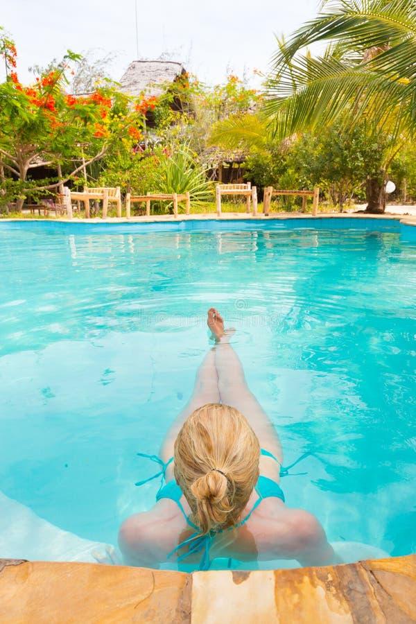 Kaukasische dame die in zwembad drijven royalty-vrije stock foto