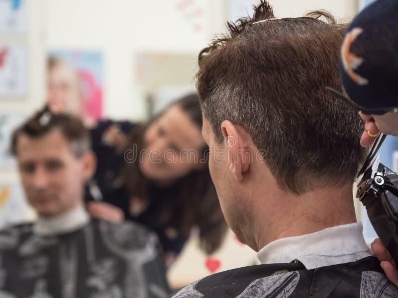Kaukasische de mensencliënt van de kappersversiering met clipper machine in herenkapper Mannelijk schoonheidsbehandelingsproces royalty-vrije stock afbeelding