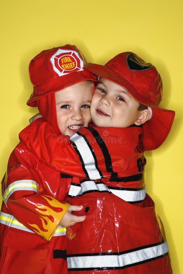 Kaukasische Doppeljungen gekleidet als Feuerwehrmänner. stockbilder