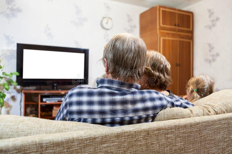 Kaukasische Eltern und Tochter, die im Couch und aufpassendem Fernsehen, lokalisierter weißer Schirm sitzt lizenzfreie stockbilder