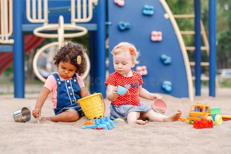 Kaukasische en Spaanse Latijnse babyskinderen die in zandbak het spelen zitten royalty-vrije stock afbeeldingen
