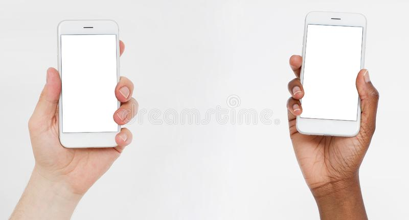 Kaukasische en zwarte de celtelefoons van de handengreep Lege het schermsmartphone De exemplaarruimte, bespot omhoog, spatie, mal stock afbeelding