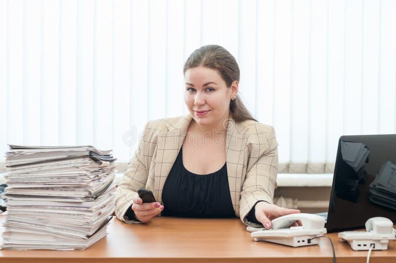 kaukasische Frau des Büro-Mädchenbüroangestellteen, die bei Tisch mit Stapel von Dokumenten sitzt lizenzfreie stockbilder