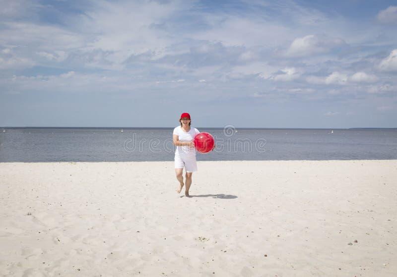 Kaukasische Frau, die auf dem sandigen Strand mit rotem Ball läuft stockfotografie
