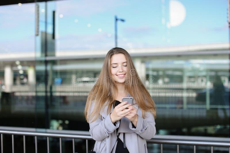 Kaukasische Frau, die durch Smartphone nahe valise und Flughafen simst stockbild