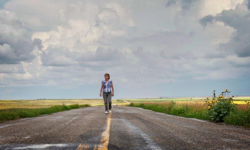 Kaukasische Frau, die mitten in der Landstraße geht lizenzfreie stockfotografie